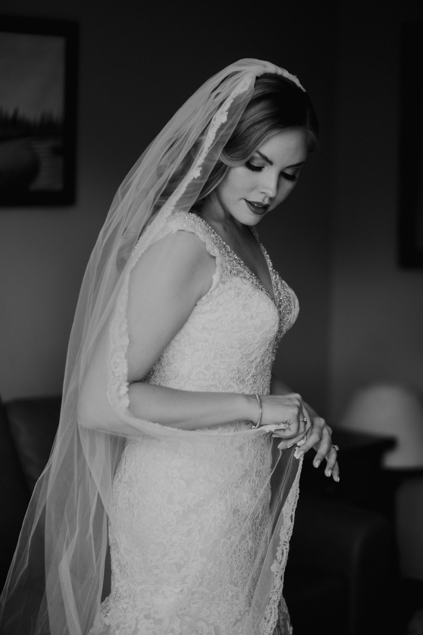 Bride fixing veil candid black and white photograph