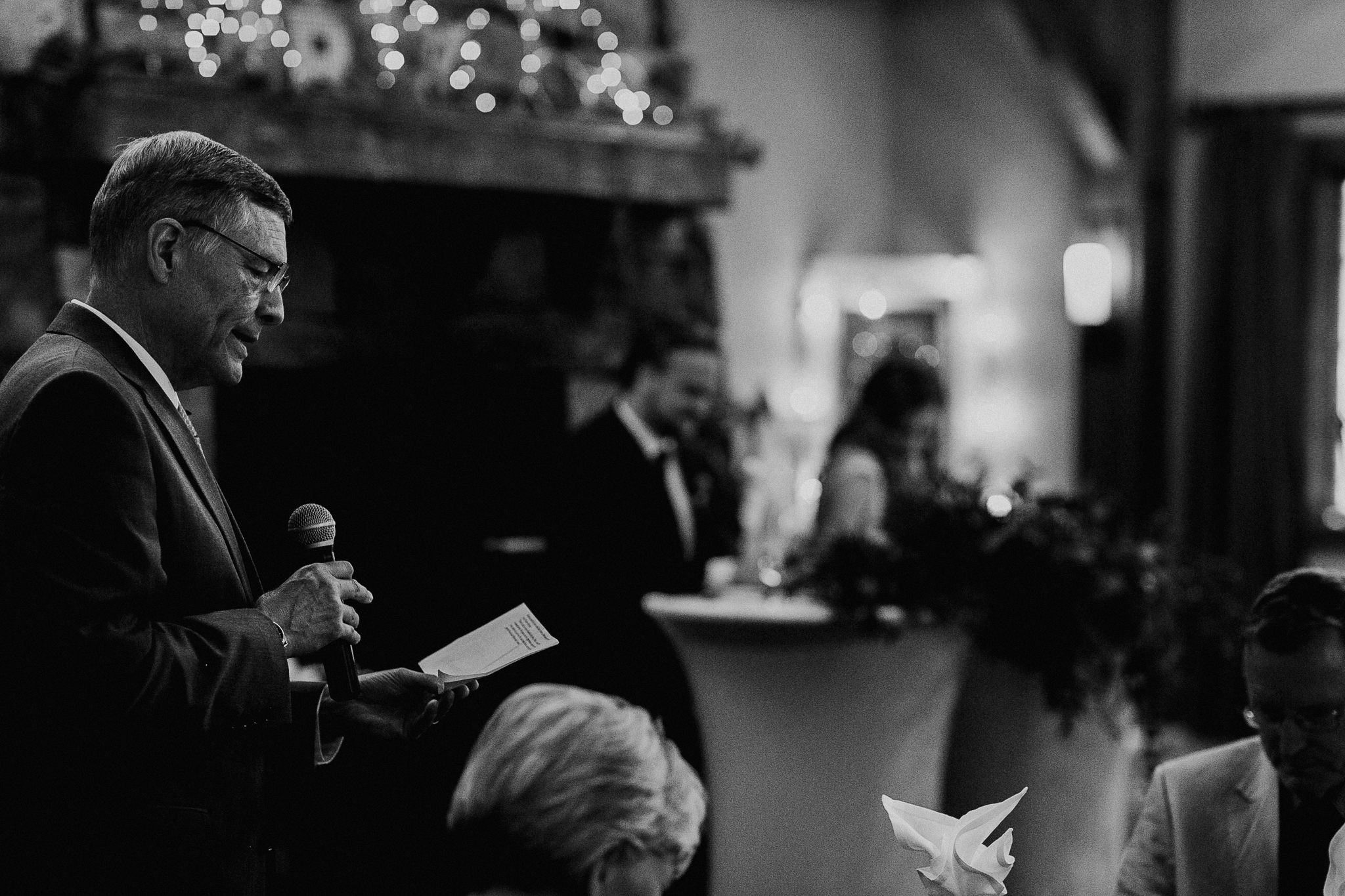 Bride and groom listen to speeches at Silvertip Resort wedding reception