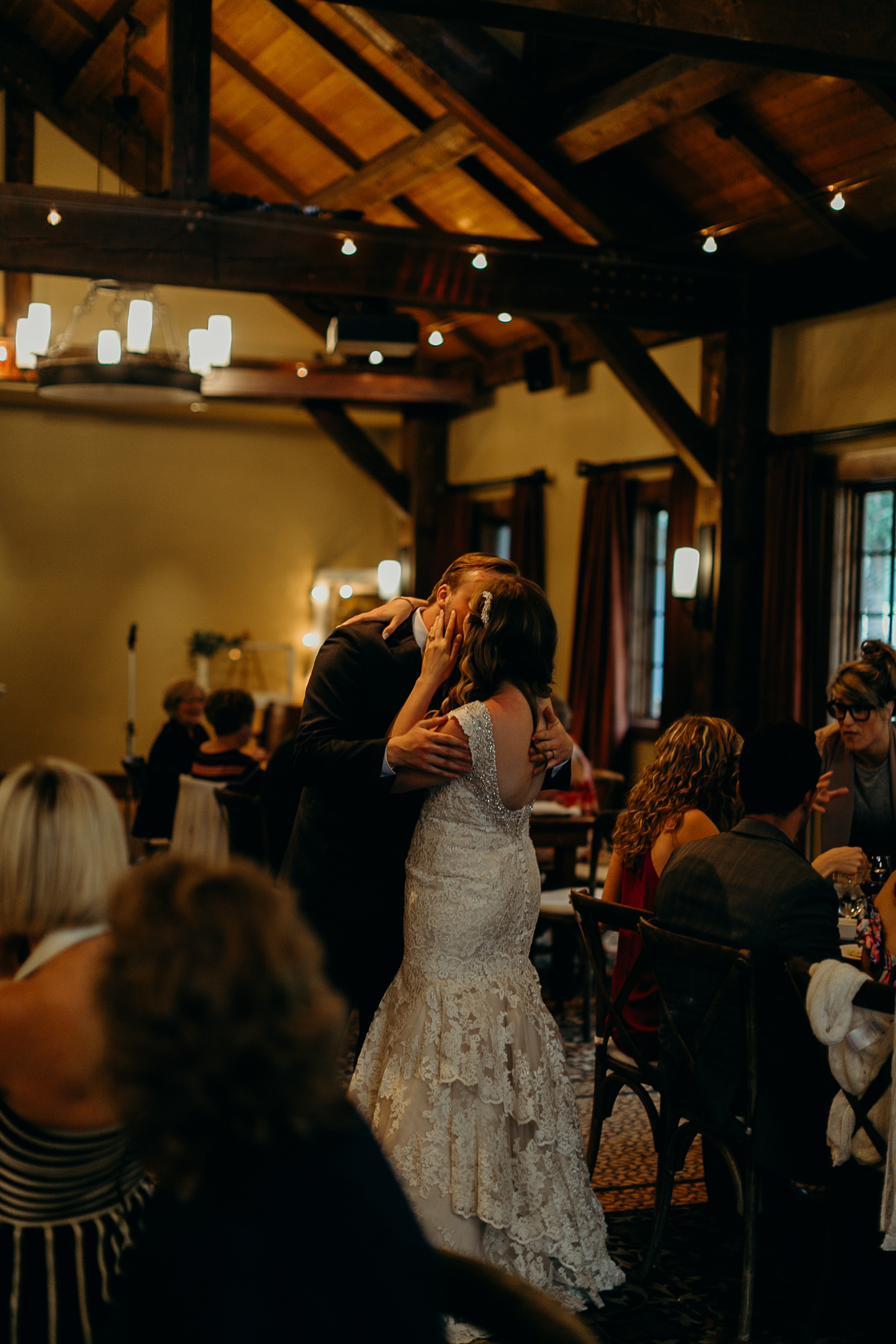 Bride and groom kiss during wedding reception at Silvertip Resort in Canmore AB