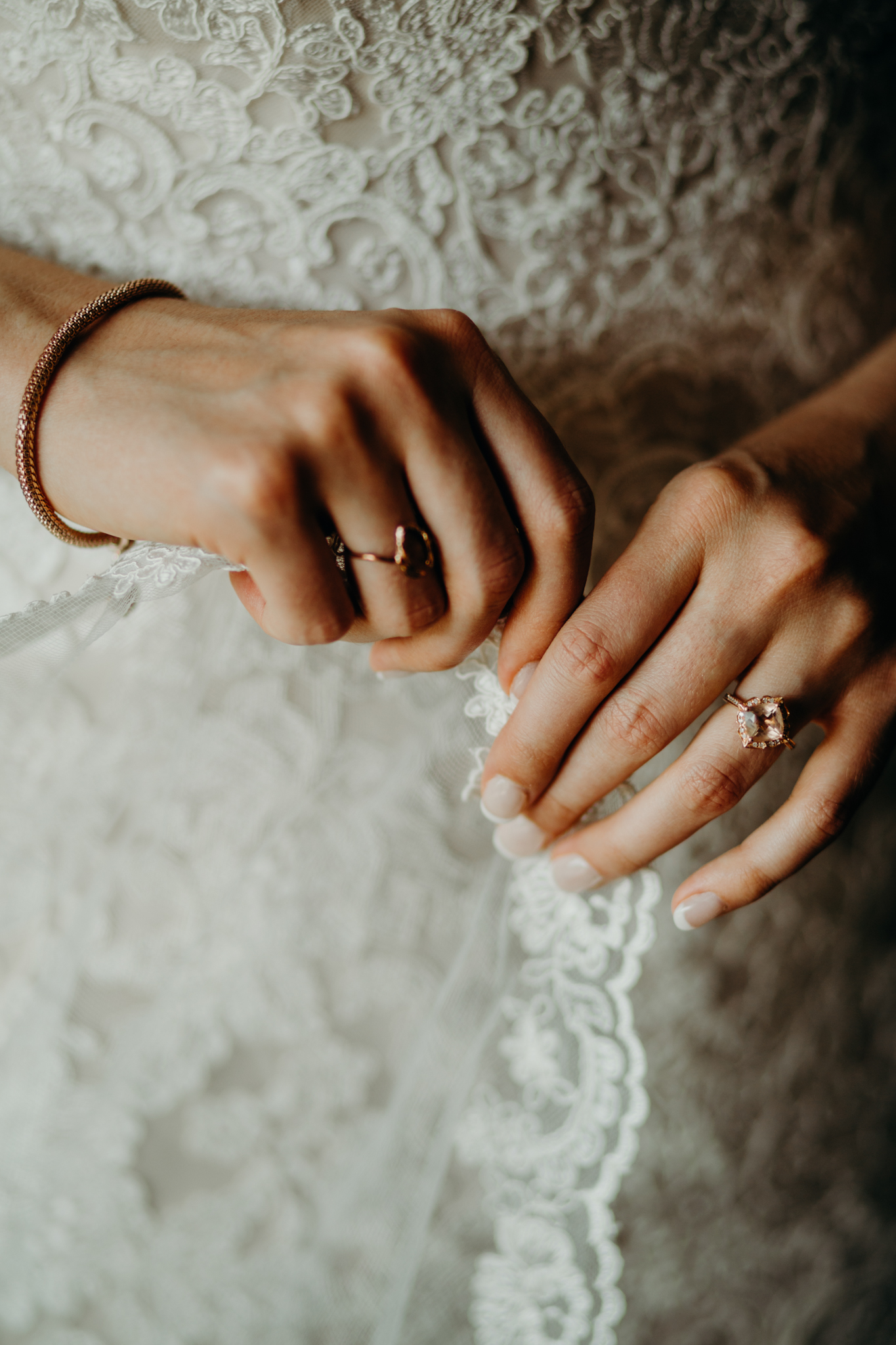 Close up of bride's hands fixing veil