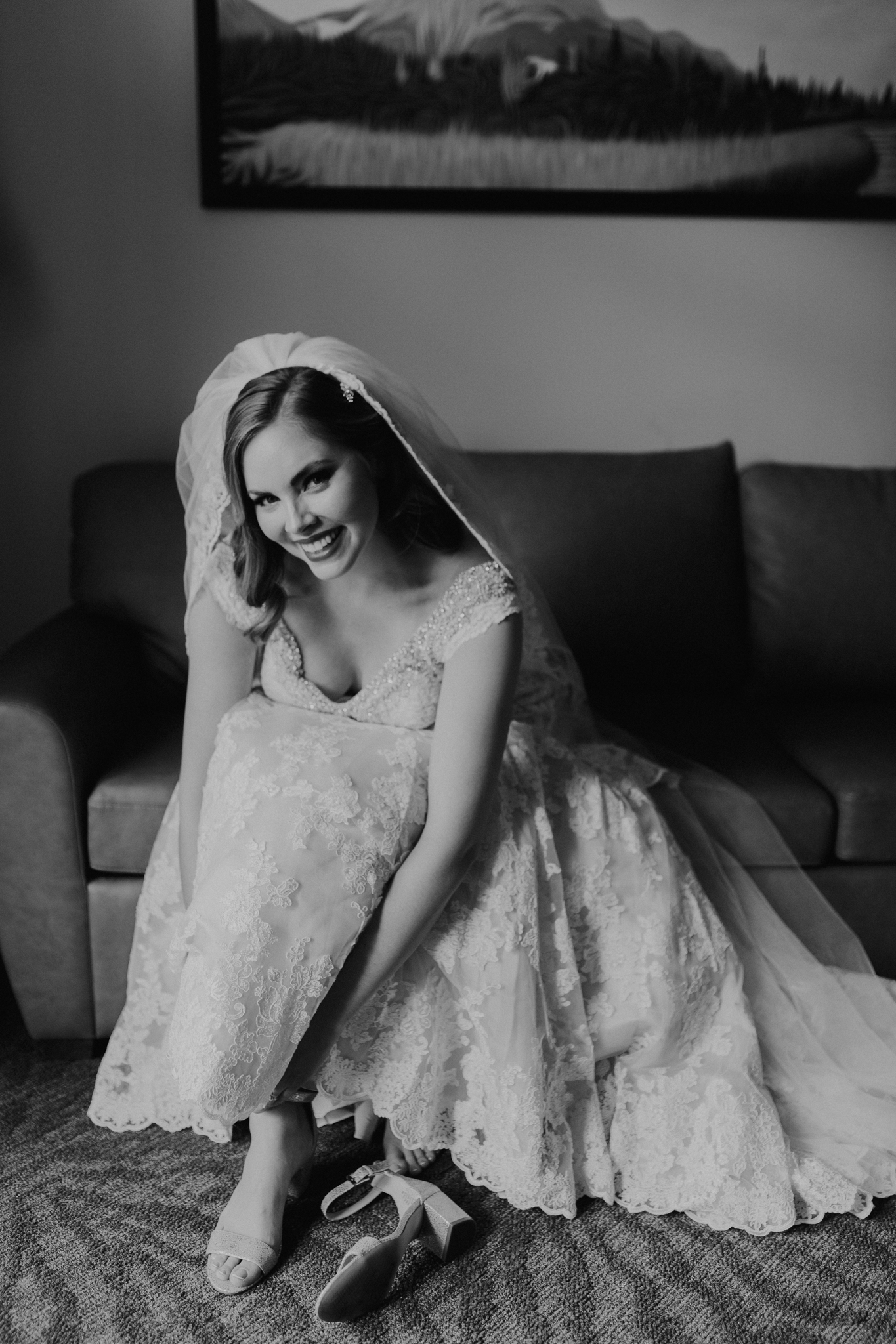 Bride sitting on couch putting on shoes at destination wedding in Canmore Alberta