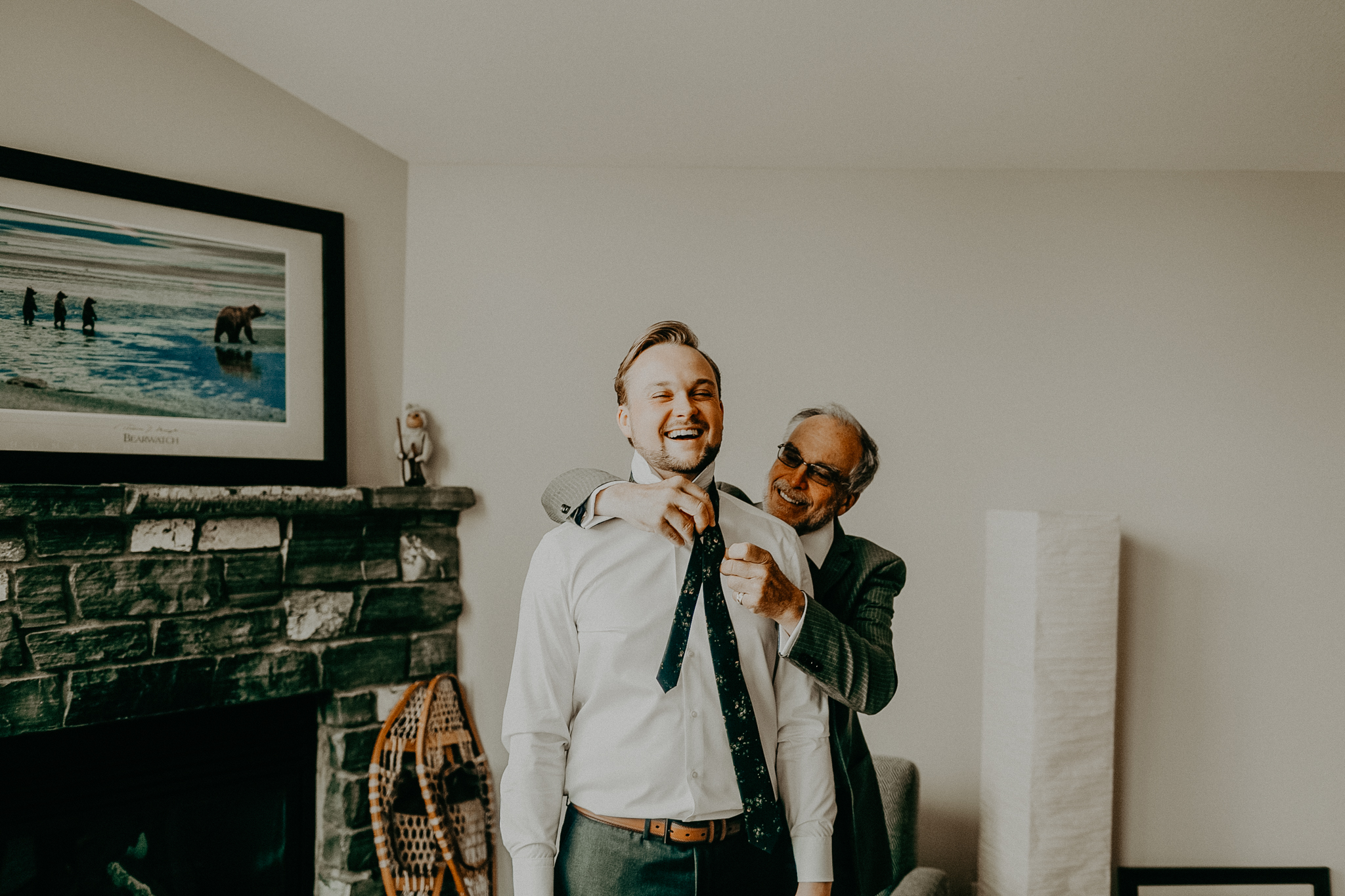 Groom's dad helps groom tie on tie in hotel room while getting ready for wedding