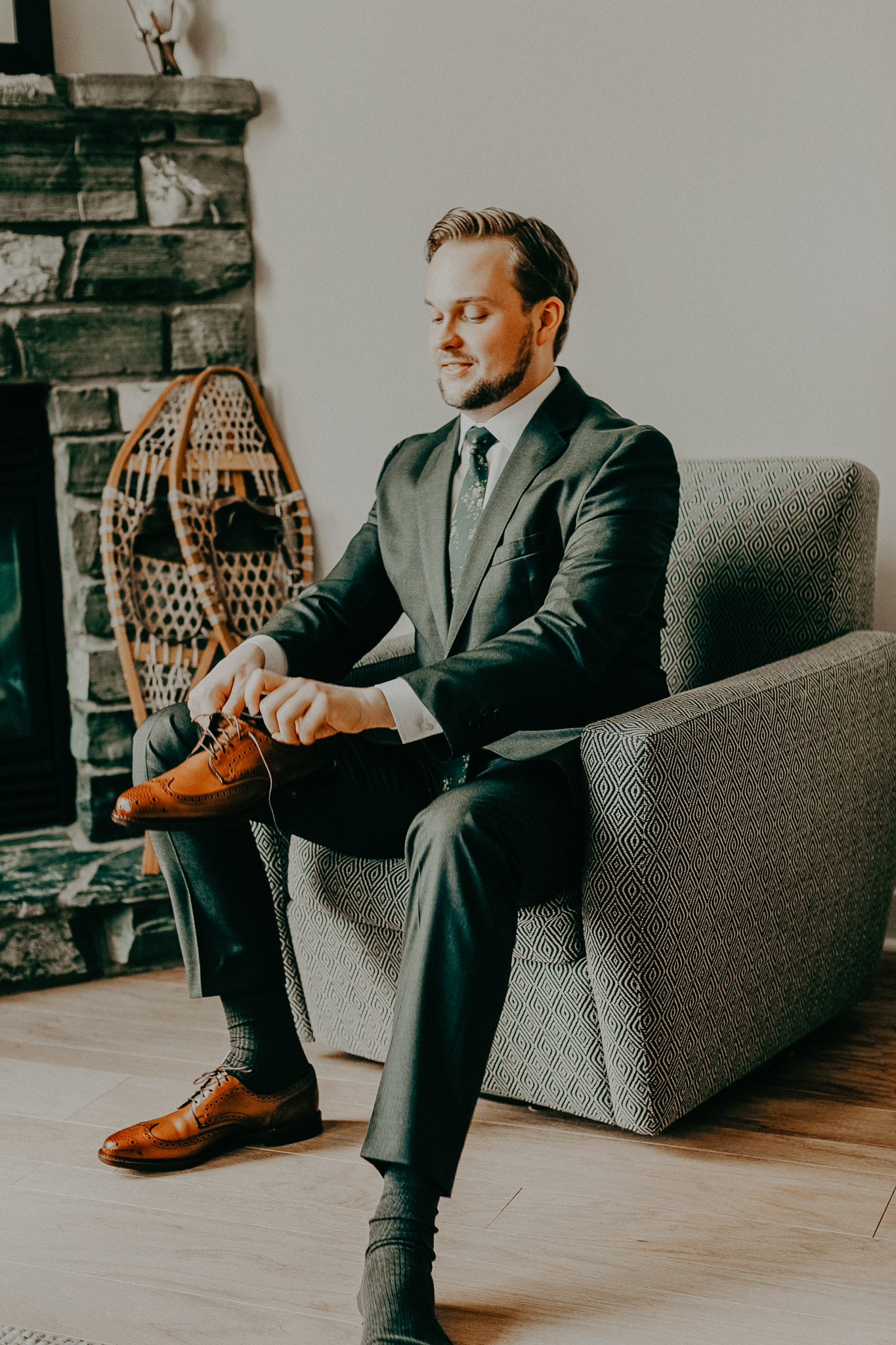 Groom sits on grey chair in grey suit and puts on brown dress shoes