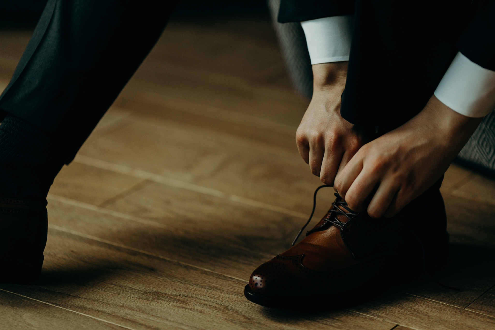 Close up of hands tying brown dress shoes