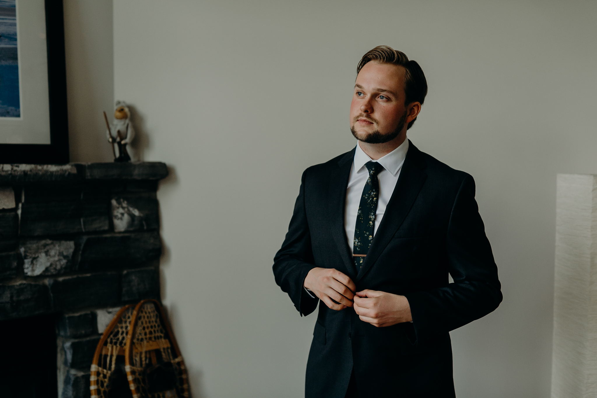 Portrait of groom buttoning jacket