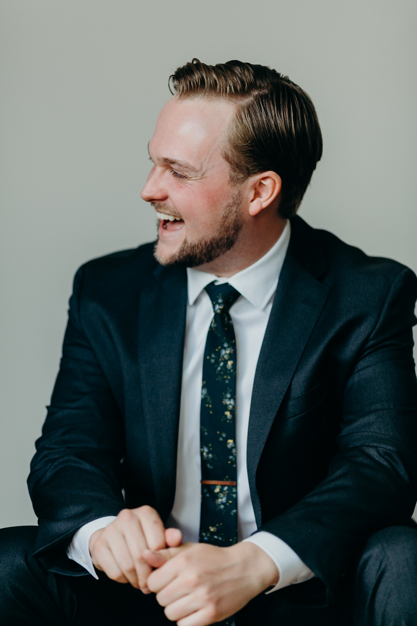 Candid portrait of groom in suit against white wall laughing
