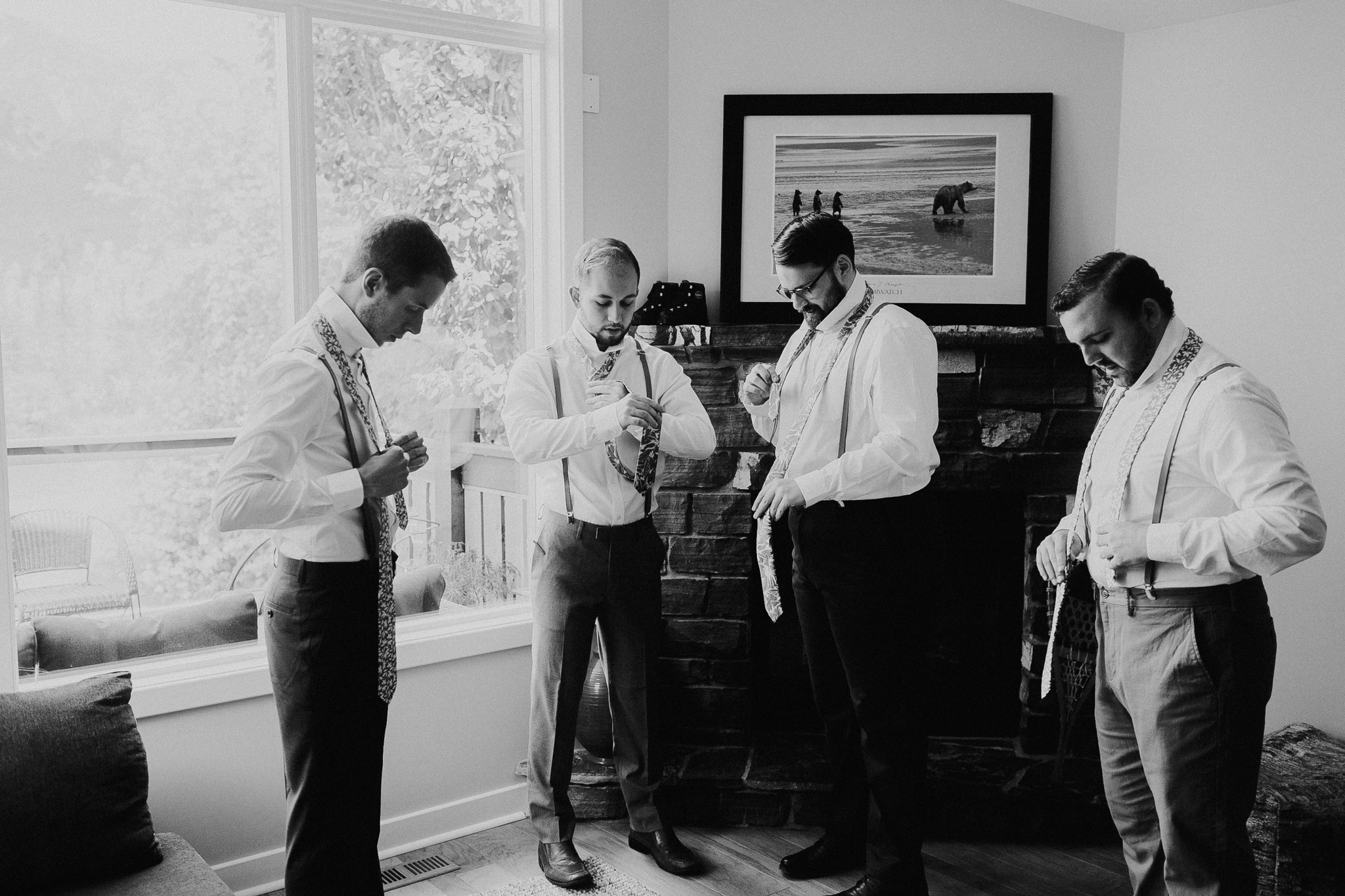 Documentary wedding photo of four groomsmen in black and white getting ready