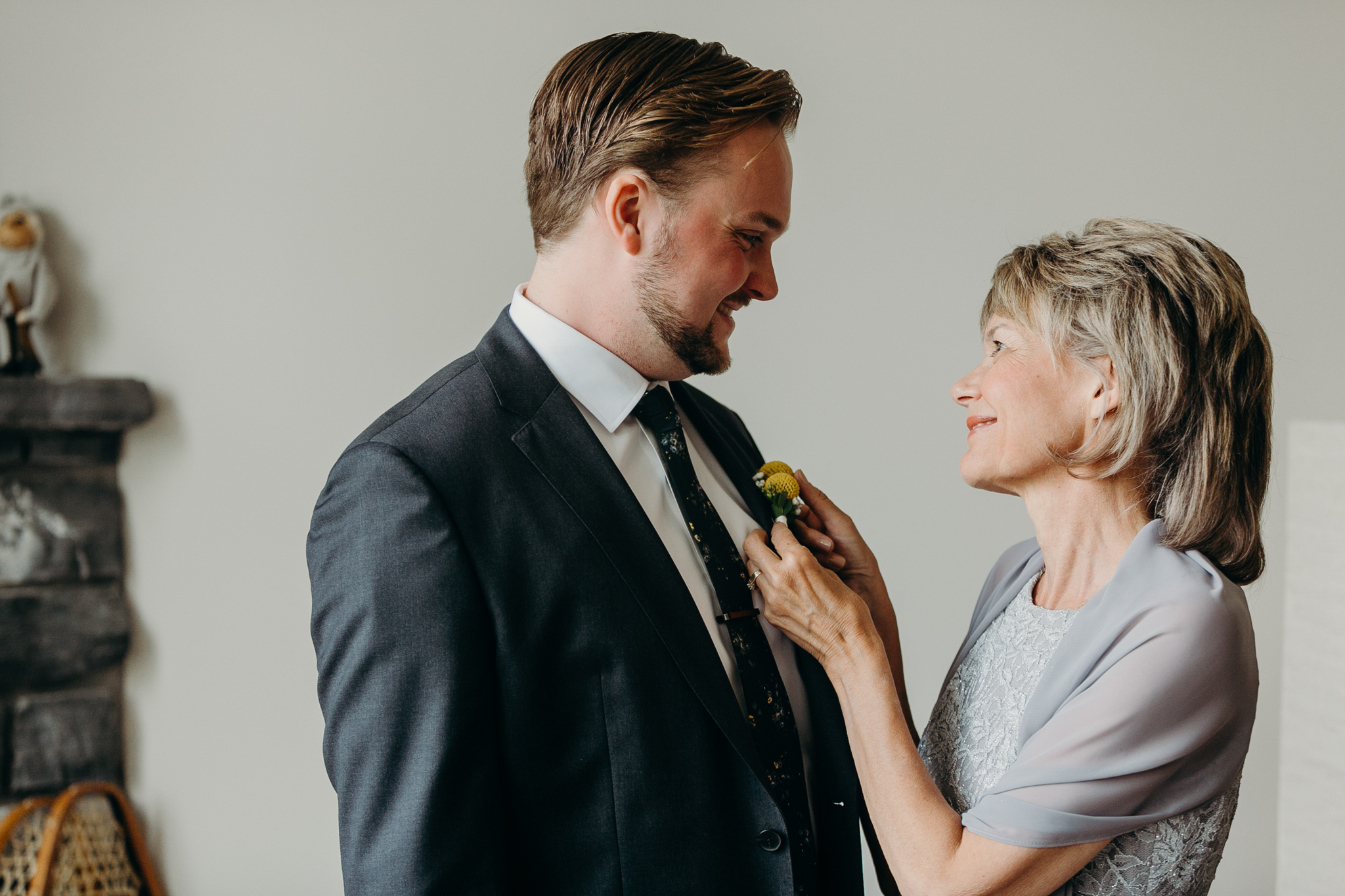 Sentimental portrait of mother looking at her son, the groom, on his wedding day