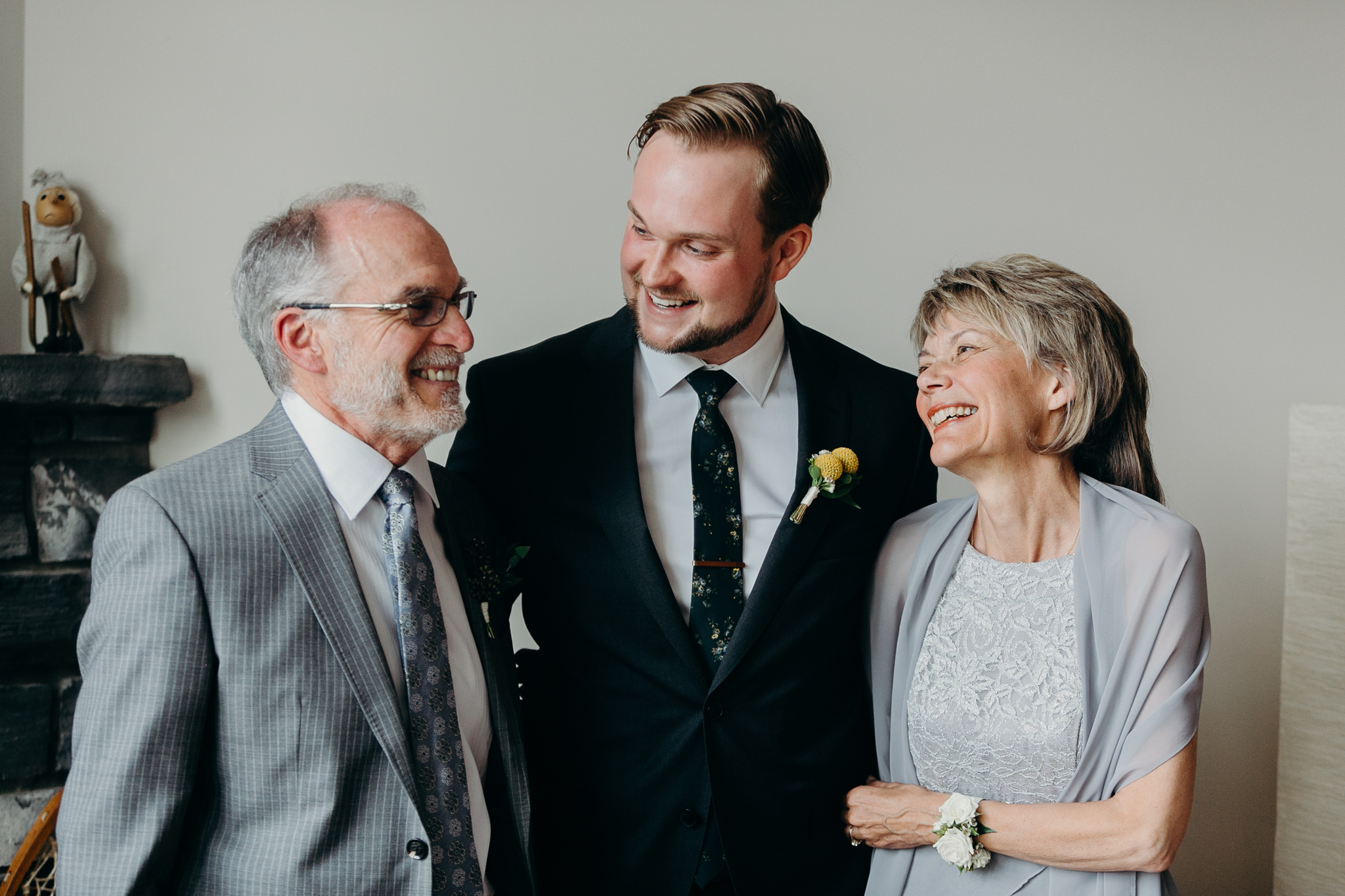 Portrait of groom looking at his father and mother before wedding candid MN wedding photographer