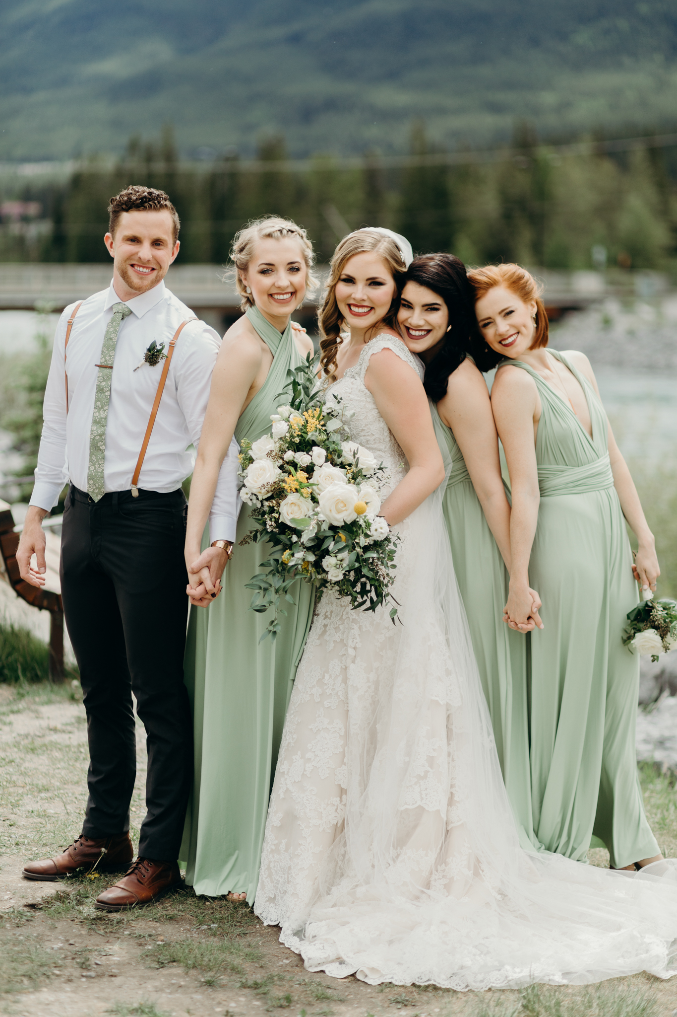 Bridesmaids post by river in green dresses