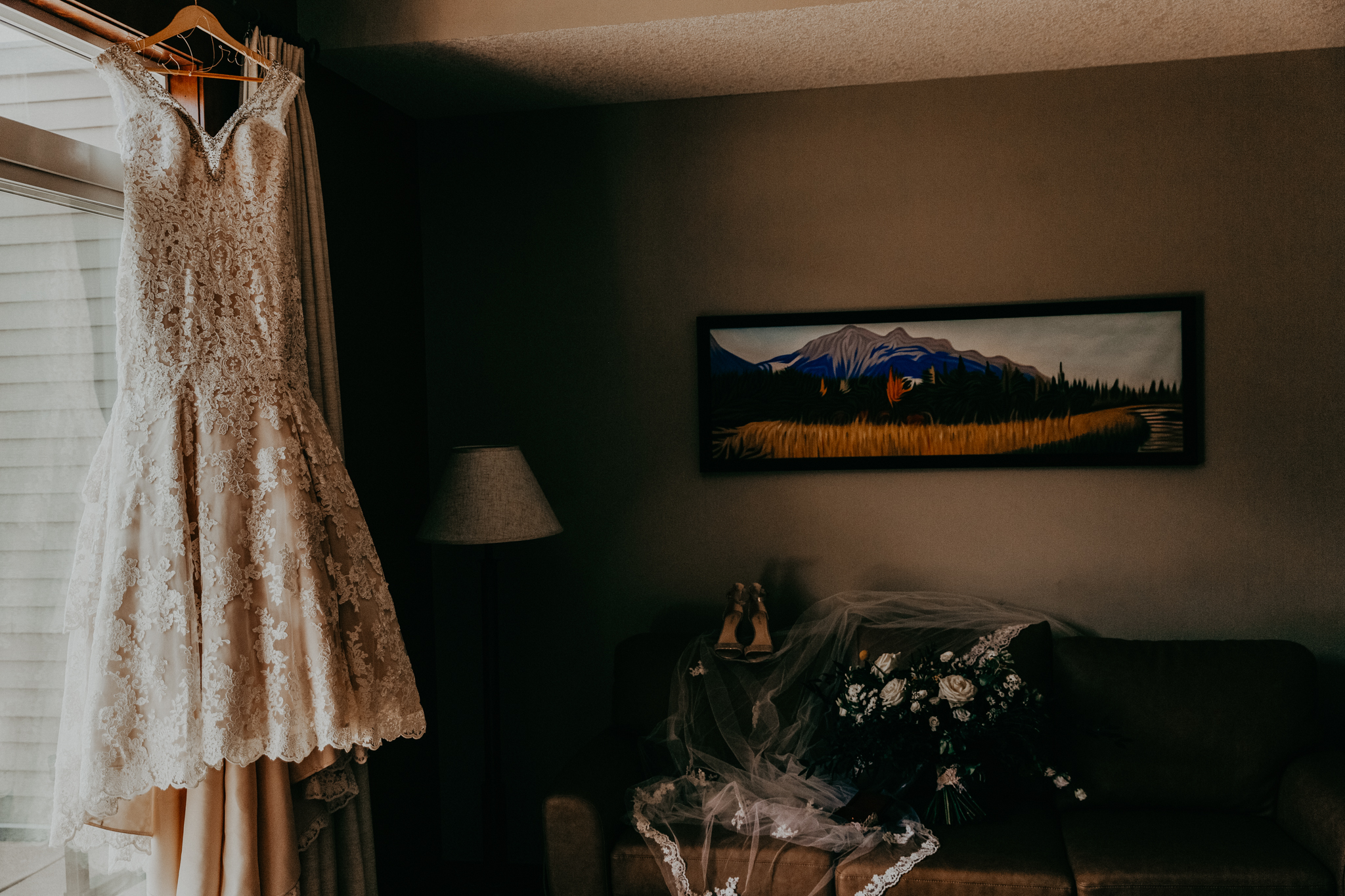 Bride's wedding dress hanging from doorframe with veil and flowers
