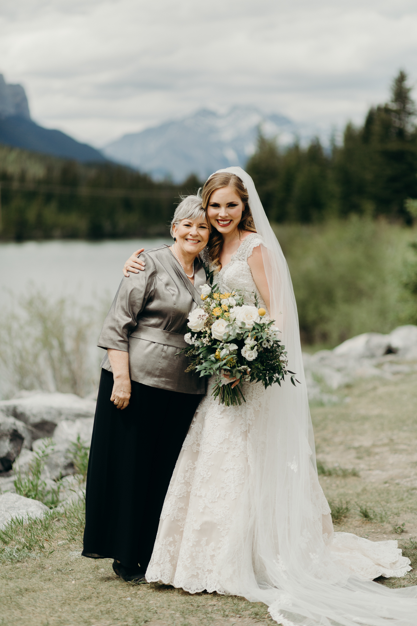 Bride and Mother of bride pose by river smiling destination wedding photographer MN