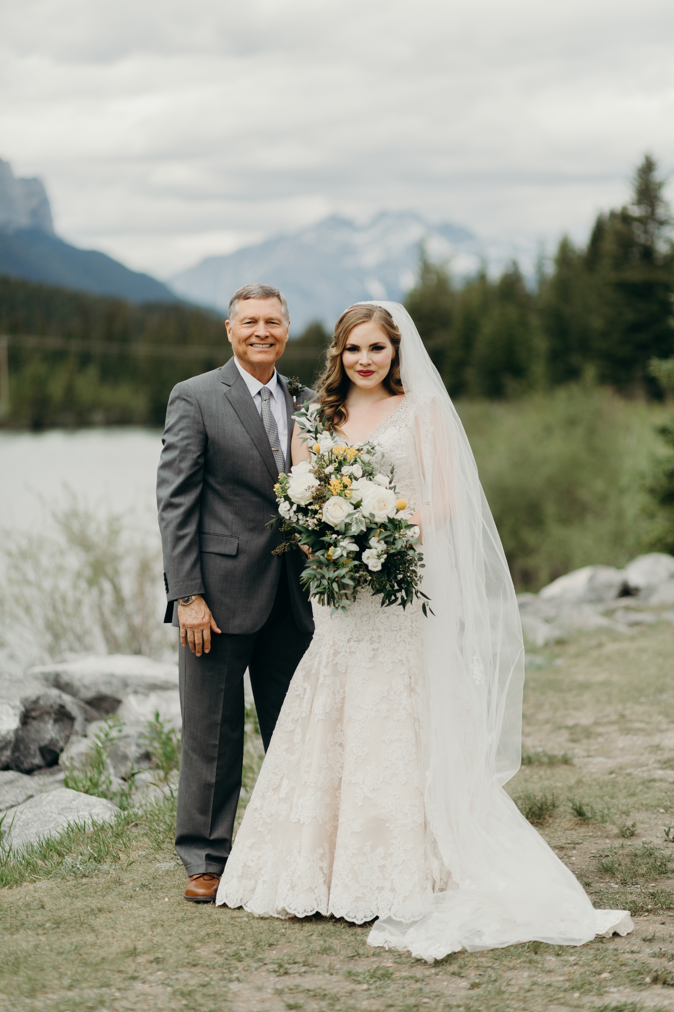 Bride and Father of bride pose by river smiling destination wedding photographer MN