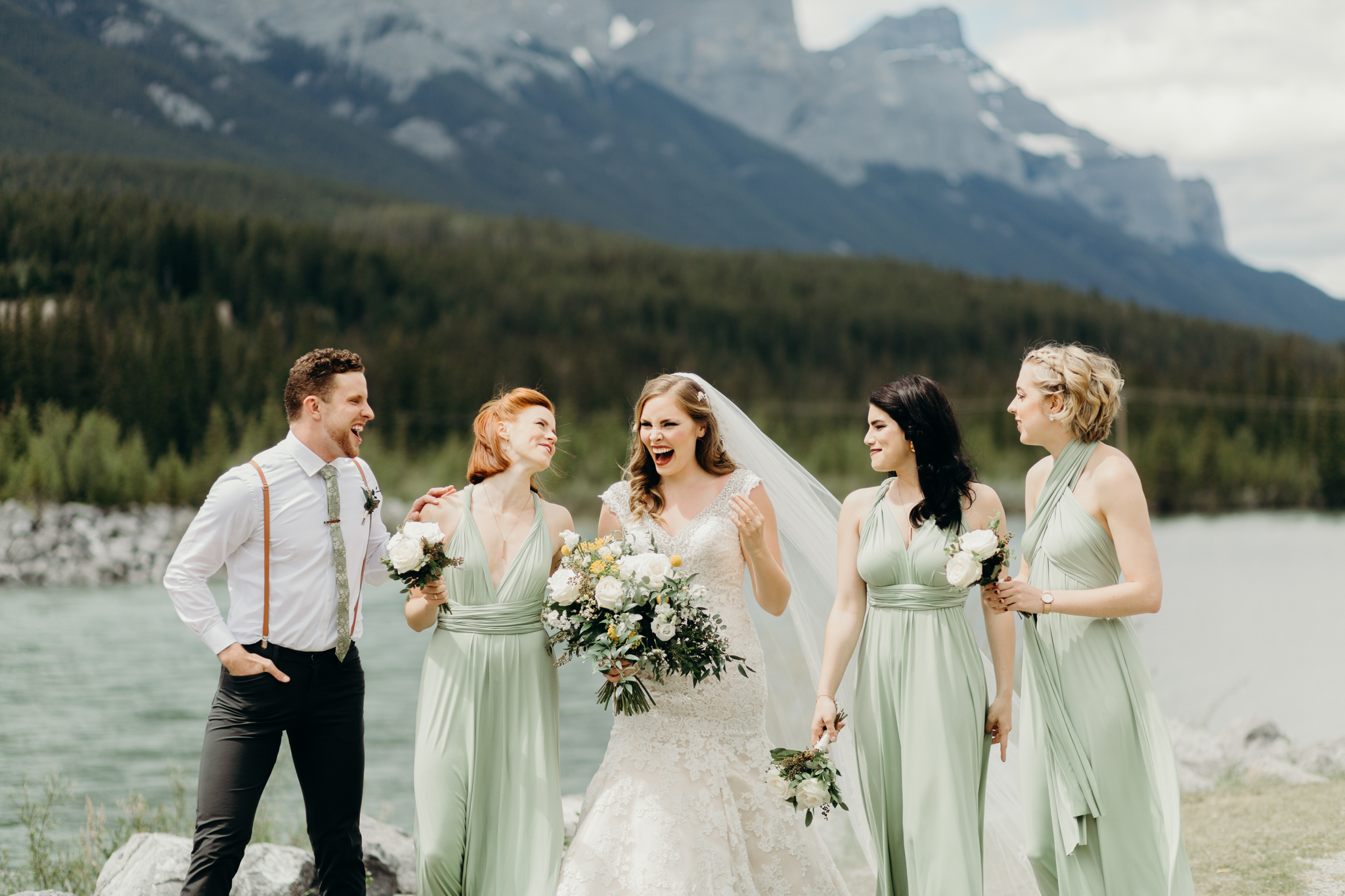 Bride and bridesmaids walk and laugh destination wedding photographer rocky mountains