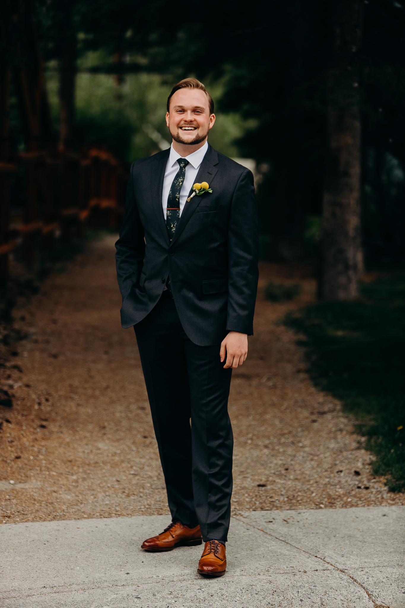 Portrait of smiling groom in suit and tie outdoors destination wedding canmore