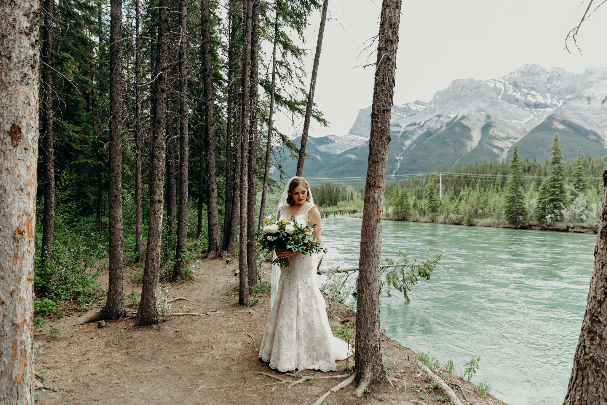 Bride stands by the Bow River holding larger flower bouquet with mountains in background