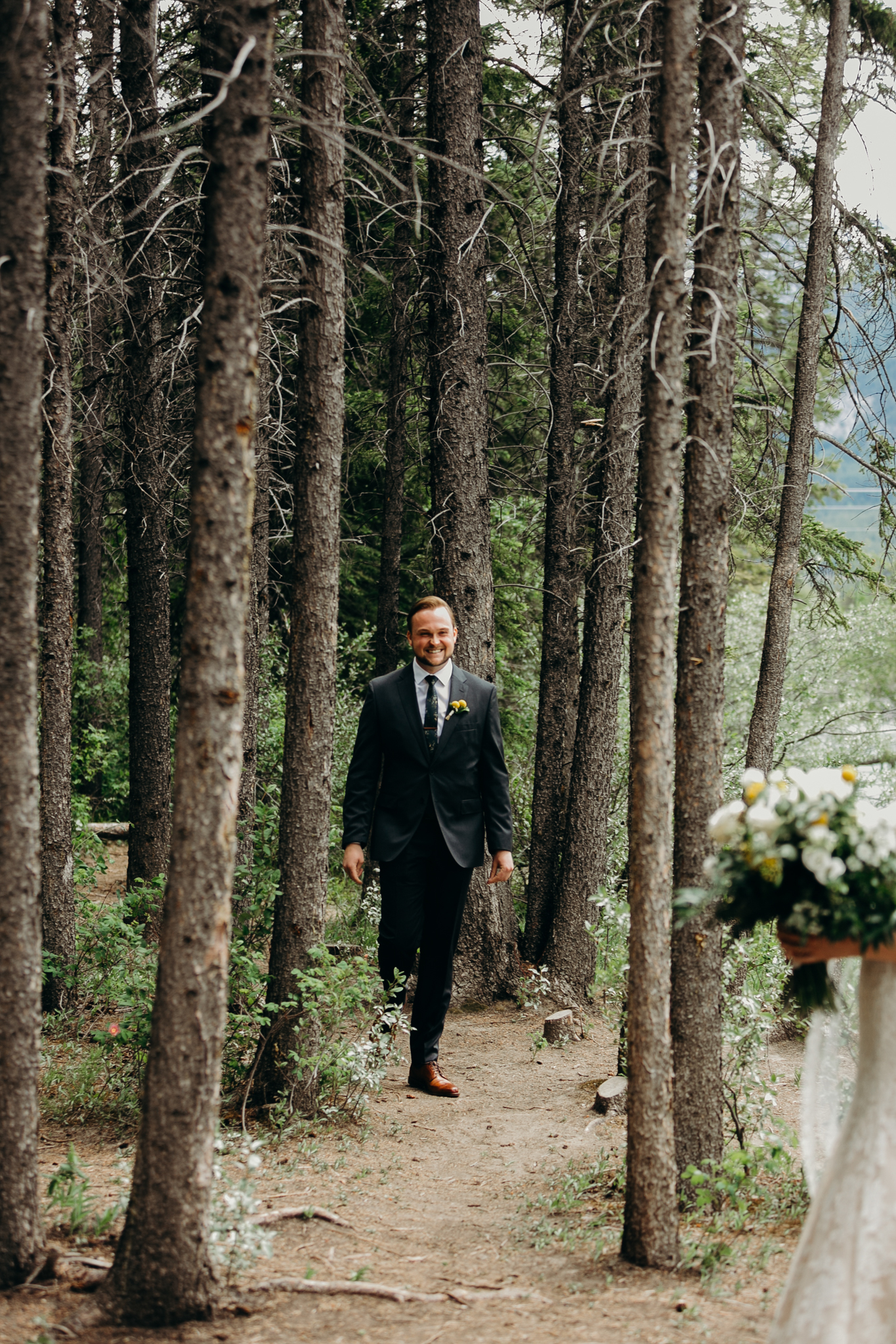 Groom walks trail through tall trees first look photograph