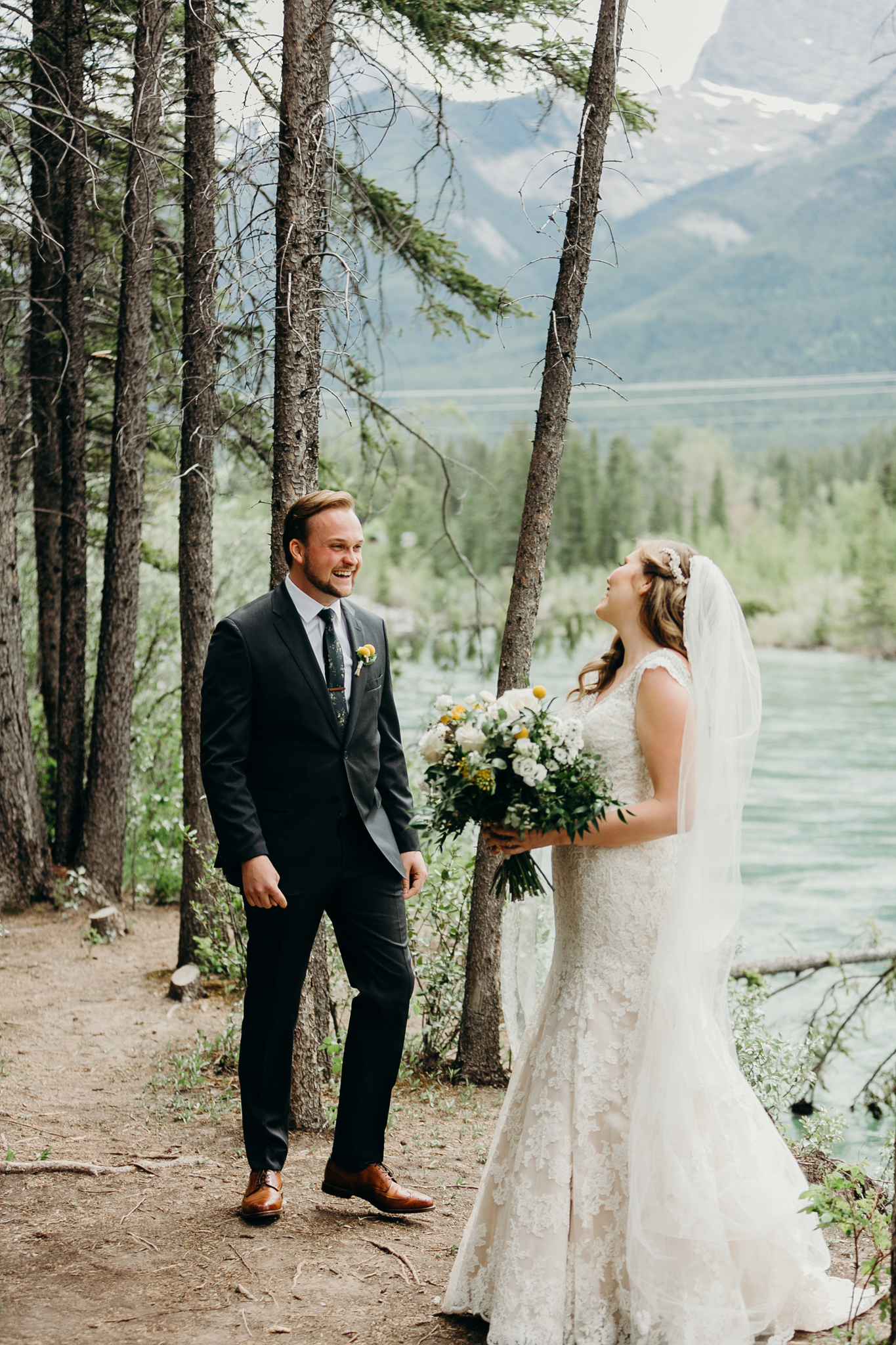 Groom sees bride during first look smiling with Bow River and mountains in background Canmore AB