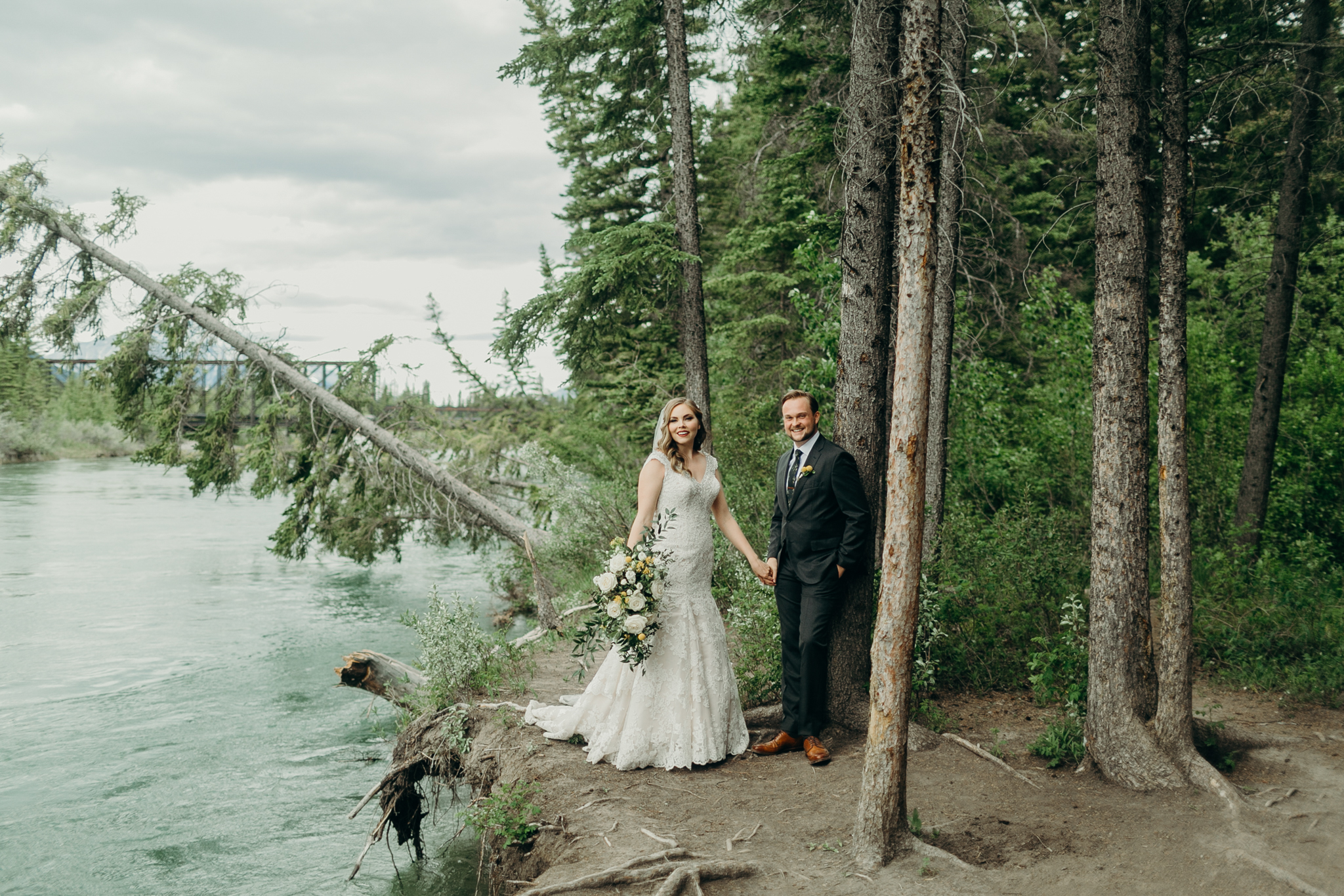 Bride and groom stand on cliff with river in background and fallen tree Canmore Bow River