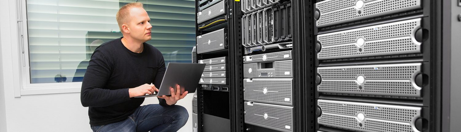 man with laptop in front of servers