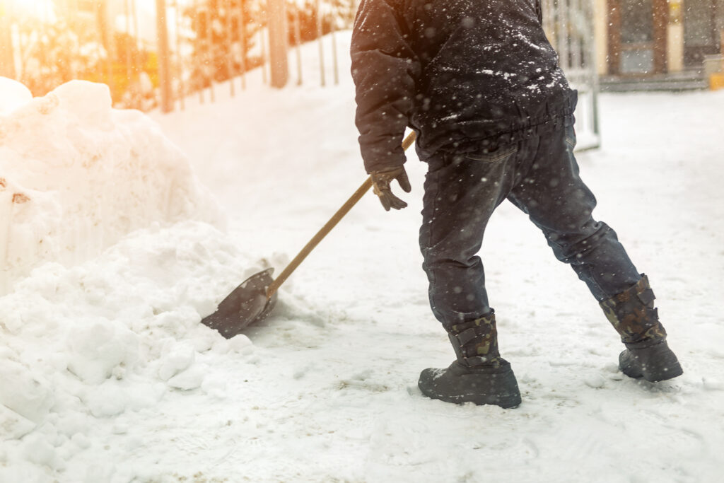 Property All worker shoveling snow from a commercial property