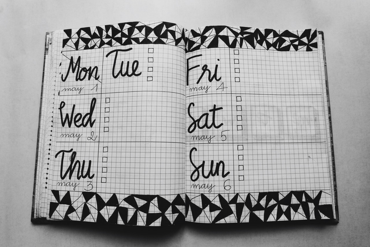 white-and-black-weekly-planner-on-gray-surface-1059383