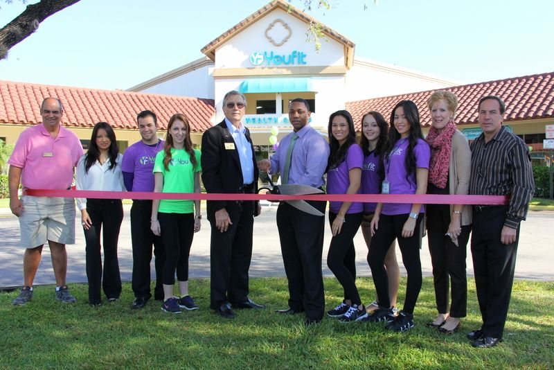 """Pictured From The Wellington Chamber of Commerce:  Bob Salerno, Evelyn Perez, Mark """"Boz"""" Bozicevic, Denise Carpenter, Carmine Marino.  Center with scissors: Monti McGill.  Purple and green T-shirts are the Youfit Health Clubs Staff."""