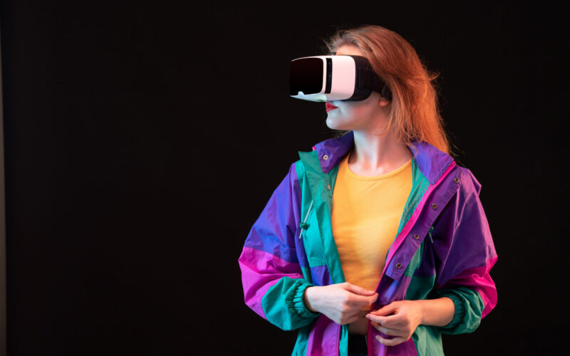 front-view-modern-young-lady-colorful-coat-orange-t-shirt-playing-virtual-reality-black-background-gaming-interactive-play