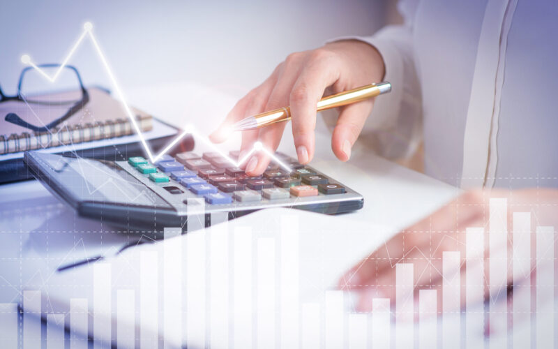 Accountant calculating profit with financial analysis graphs. Notebook, glasses and calculator lying on desk. Accountancy concept. Cropped view.