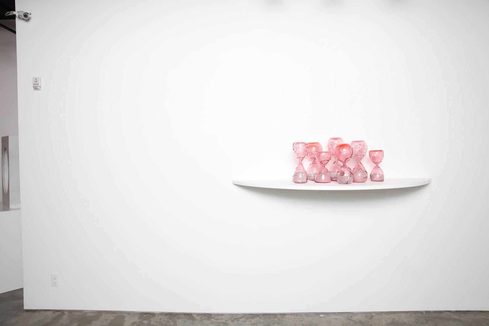 Installation art view at Garis & Hahn Gallery in New York City of glass pink hourglasses by Zoe Buckman.