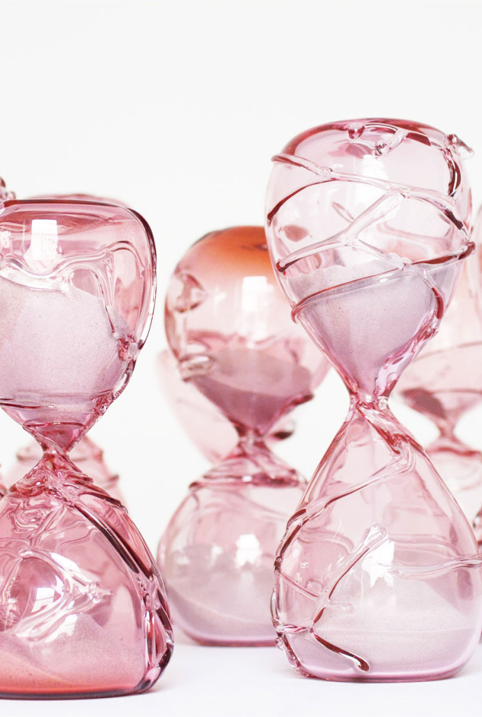 Close–up image of pink hand blown glass sculptures of hourglasses to represent the temporary nature of life.