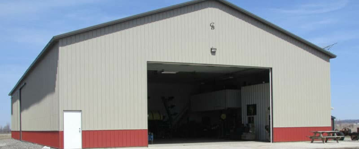 large tan and red pole building machine shed on farm
