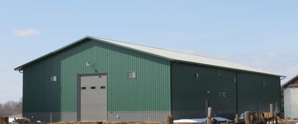 green two story farm post frame building