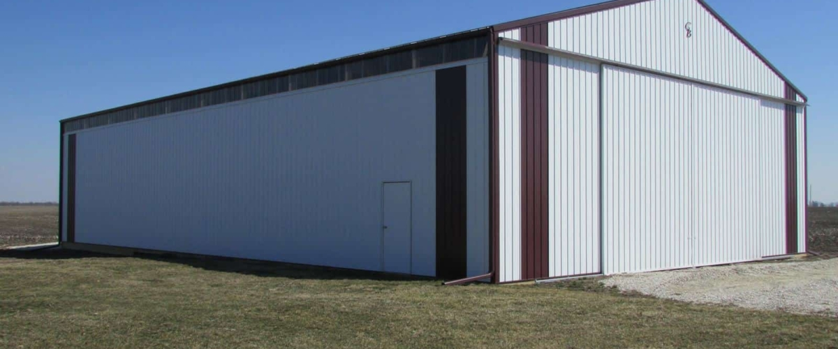 large white machine shed pole barn with sliding door