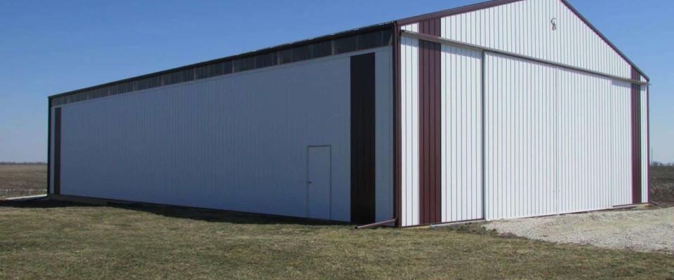 large white machine shed pole barn with sliding door