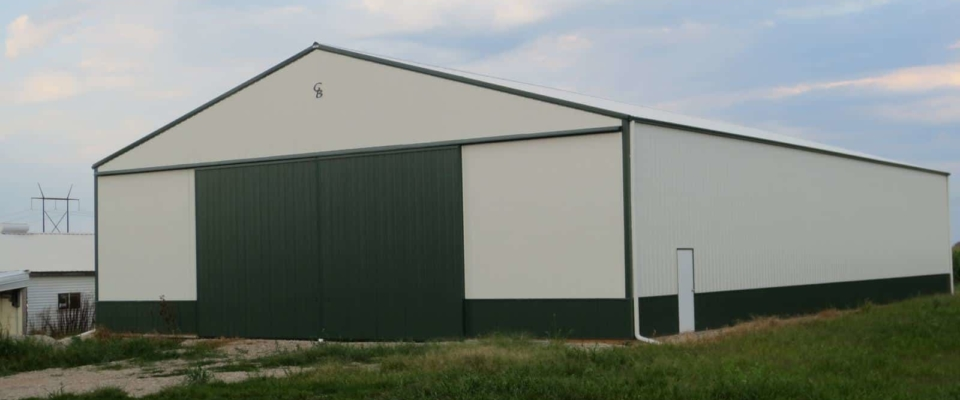 large green machine shed storage building on farm in iowa