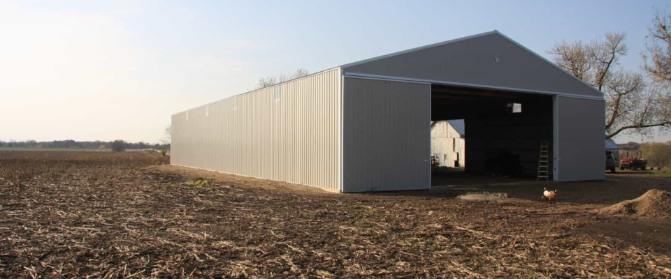 gray metal storage pole building in field