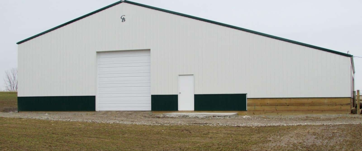 white and green livestock post frame building
