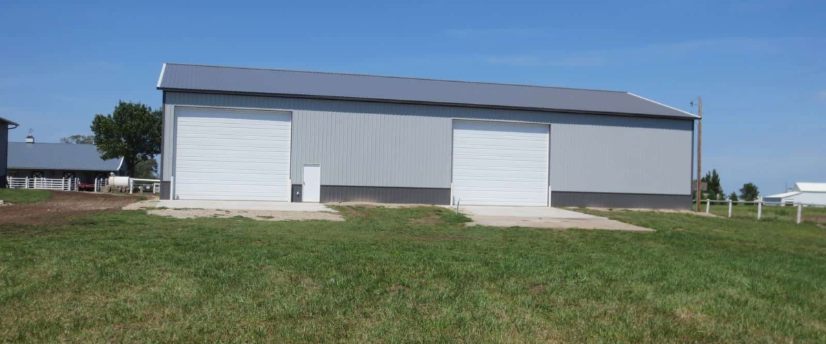 gray machine shed farm building with white doors