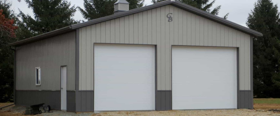 tan and gray pole barn garage two white doors