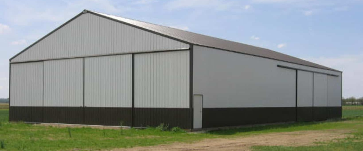 white and green machine shed with large sliding doors