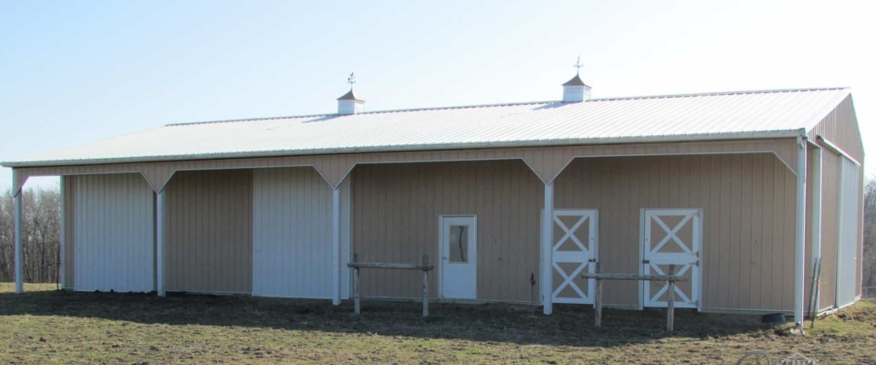 white and cream colored horse barn small post frame building