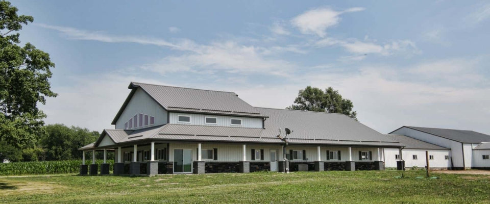 blue and gray pole barn house with horse arena attached