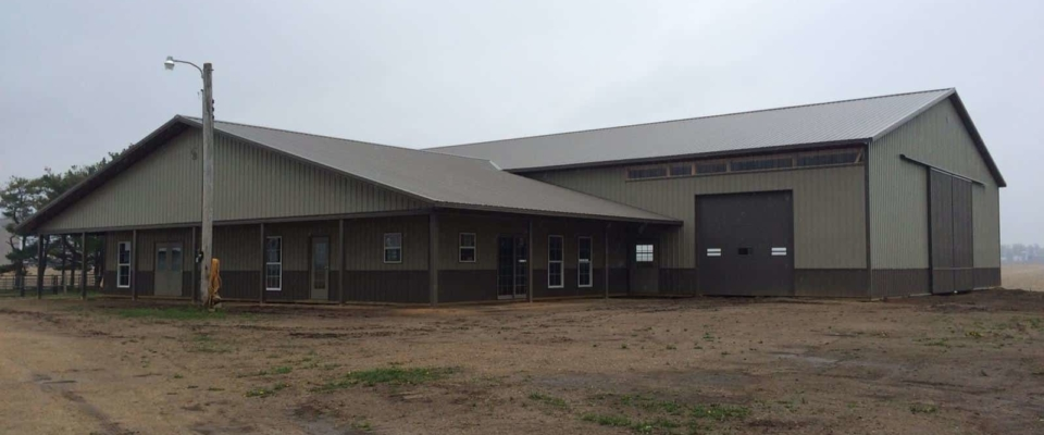 tan and brown horse barn with large arena post frame building