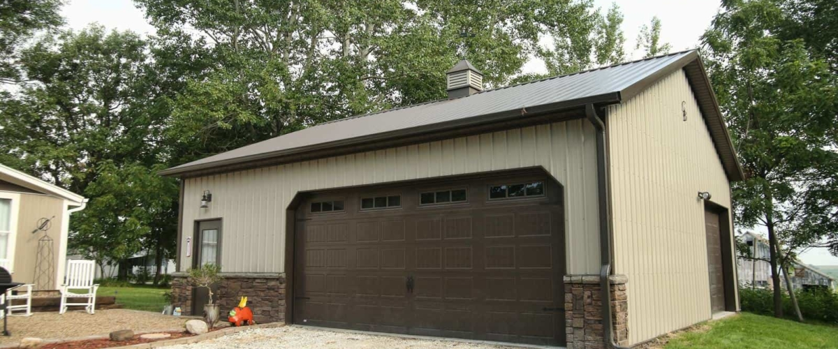 brown and tan post frame garage large door
