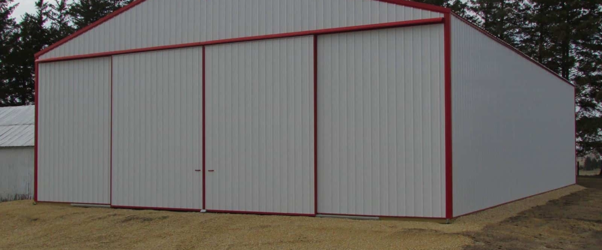 large white and red pole barn machine shed on farm