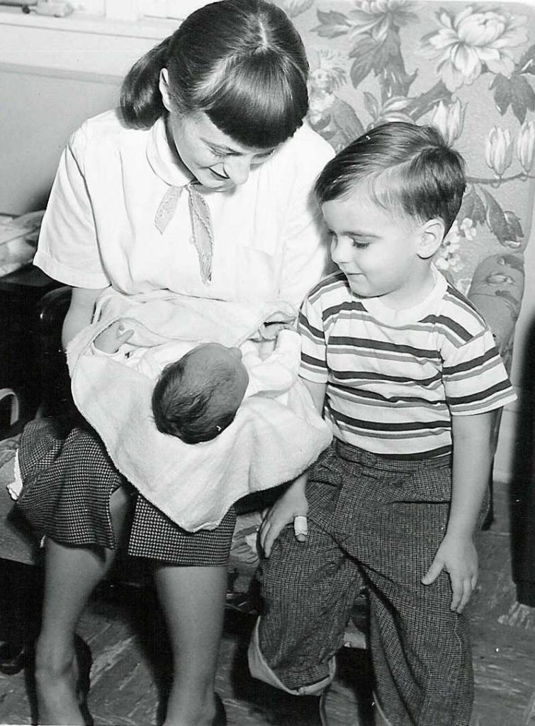 Joan Ruth Sullivan Peeples, holding infant daughter Ruth L. Peeples, as son Stephen K. Peeples, age 2 1/2, looks on. Neenah, Wisconsin, late January-early February 1955. Photo: Zelda Ruth Sullivan.