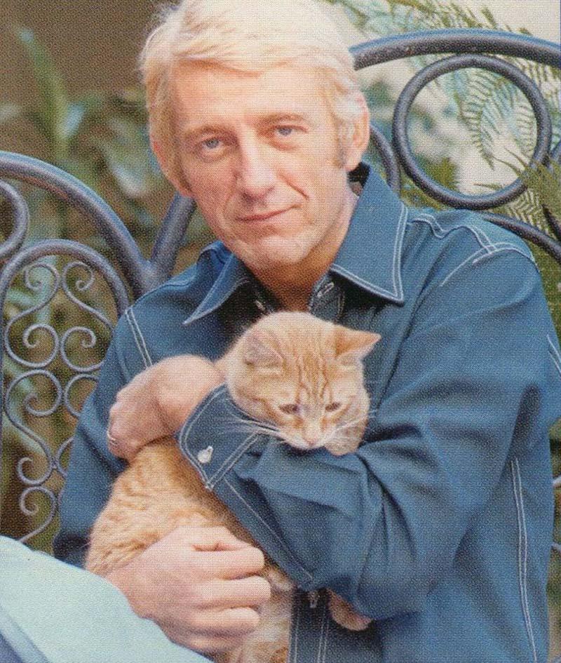 Rod McKuen gets warm with a feline friend.