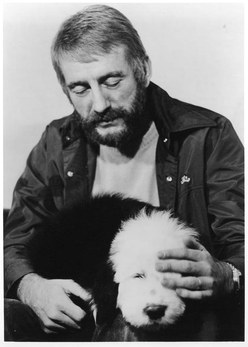 Rod McKuen gets warm with a canine friend.