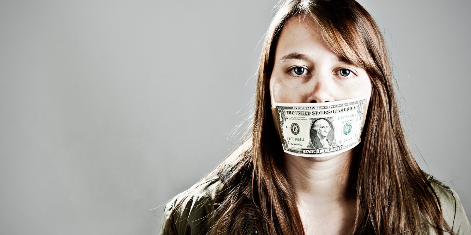 This young woman seems to have accepted being gagged with a US one dollar bill; she'll keep quiet if she's paid to!